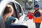 Woman watching roadside mechanic fill gas tank