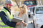 Roadside mechanic and woman reviewing paperwork