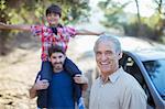 Portrait of happy multi-generation men outside car