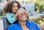 Granddaughter surprising grandmother on patio