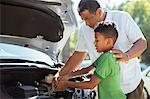 Grandfather and grandson repairing car engine