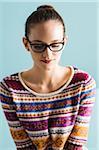 Close-up portrait of teenage girl wearing horn-rimmed eyeglasses, looking downwards, studio shot on blue background