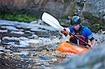 Mid adult man kayaking on river rapids