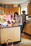 Three generation females preparing food in kitchen