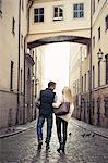 Rear view of couple walking on city street