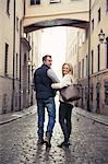 Full length of happy couple walking on city street