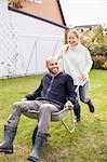 Happy woman pushing man in wheel barrow at yard
