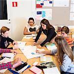 Teacher explaining chart to high school student in classroom