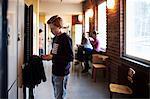 High school boy using mobile phone by locker