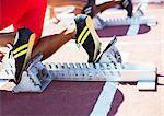 Runner's feet in starting blocks on track