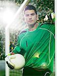 Goalie holding soccer ball in net