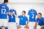 Soccer players shaking hands in locker room