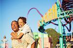 Enthusiastic couple hugging at amusement park