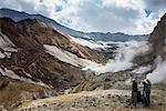 Tourists standing by smoking fumaroles on Mutnovsky volcano, Kamchatka, Russia, Eurasia