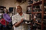 Hat maker holding top hat mould in workshop