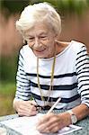 Senior woman drawing in retirement villa garden