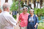 Senior man photographing friends in retirement villa garden