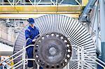 Engineer inspecting turbine in workshop