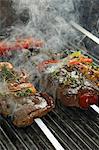 Beef steaks being barbecued on skewers