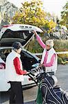 Senior female friends loading golf bag into car boot