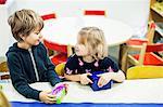 Kindergarten kids looking at each other in art class