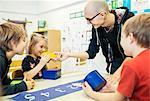Happy teacher assisting students in art class at kindergarten