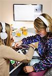 Sisters listening music on digital tablets in living room