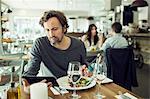 Mature man using digital tablet in restaurant