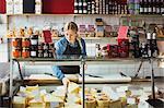 Saleswoman working at display cabinet in supermarket