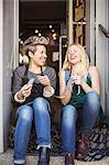 Happy female fashion designers sitting at studio doorway
