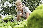 Woman planting vegetables in garden