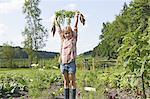 Girls in garden holding vegetables