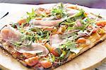 Pizza with ham and arugula (Eruca sativa)