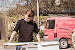Female carpenter examining wooden plank outdoors
