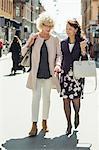 Full length of senior female friends walking on street