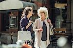 Senior women conversing while walking on city street