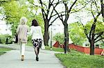 Rear view of senior female friends walking at garden path