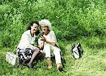 Full length of senior women using mobile phone on grass