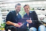 Smiling business people sharing digital tablet in cafe