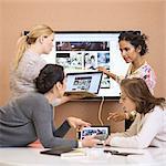 Businesswomen discussing presentation in creative office
