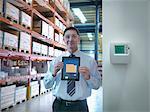 Portrait of proud office worker showing energy saving on digital tablet in factory