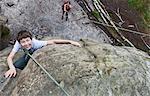 High angle view of boy rock climbing boulder