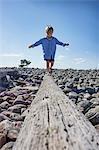 Boy balancing on log on beach