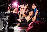Group of friends dancing in front of  DJ in nightclub