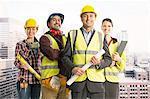Portrait of confident construction workers in urban window