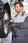 Repairman adjusting car's wheel in workshop