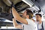 Male repair workers examining car in workshop