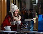 Christmas shopper using phone at coffee shop.