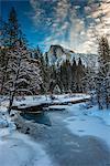 Winter view over icy Tenaya creek with Half Dome mountain behind, Yosemite National Park, California, USA