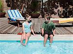 Boy and girl on edge of swimming pool